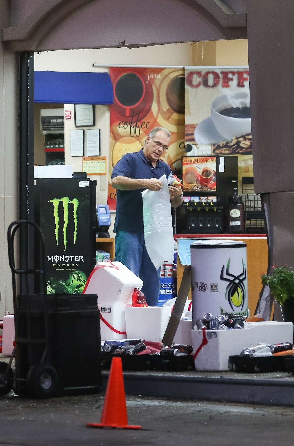 A man cleans up debris from an overnight smash-and-grab burglary at a Shell station, at the intersection of the Katy Freeway and Cortandt Street, Thursday, Nov. 17, 2016, in Houston, Texas.
