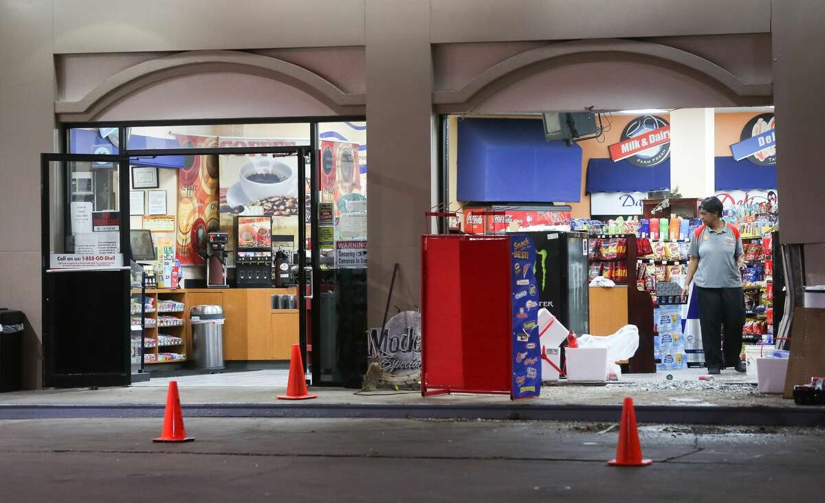 An employee looks at damage from an overnight smash-and-grab burglary at a Shell station, at the intersection of the Katy Freeway and Cortandt Street, Thursday, Nov. 17, 2016, in Houston, Texas.