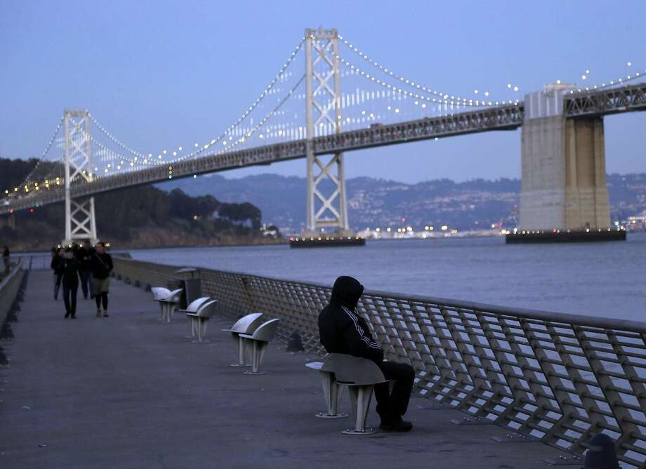 A man sits bundled up as he gets a view of the San Francisco Oakland Bay Bridge on Thursday, Dec. 5, 2013, in San Francisco. Parts of the U.S. are getting a blast of wintry weather, some experiancing frigid temperatures. (AP Photo/Marcio Jose Sanchez) Photo: Marcio Jose Sanchez, Associated Press