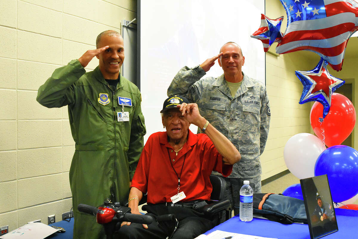 Lt. Col Tim Lambert, left, Tuskegee Airman Larry Brown and Master Sgt. Mike Fuentes all salute for the audience. Tuskegee Airman Larry Brown visited Klein High School Wednesday afternoon and visited with students about being a African American pilot in 1940 during World War II