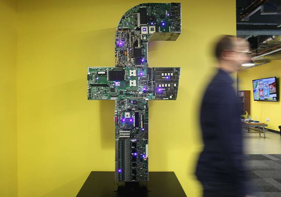 The letter 'f' stands in a corner of the Facebook offices in Cambridge, Mass.