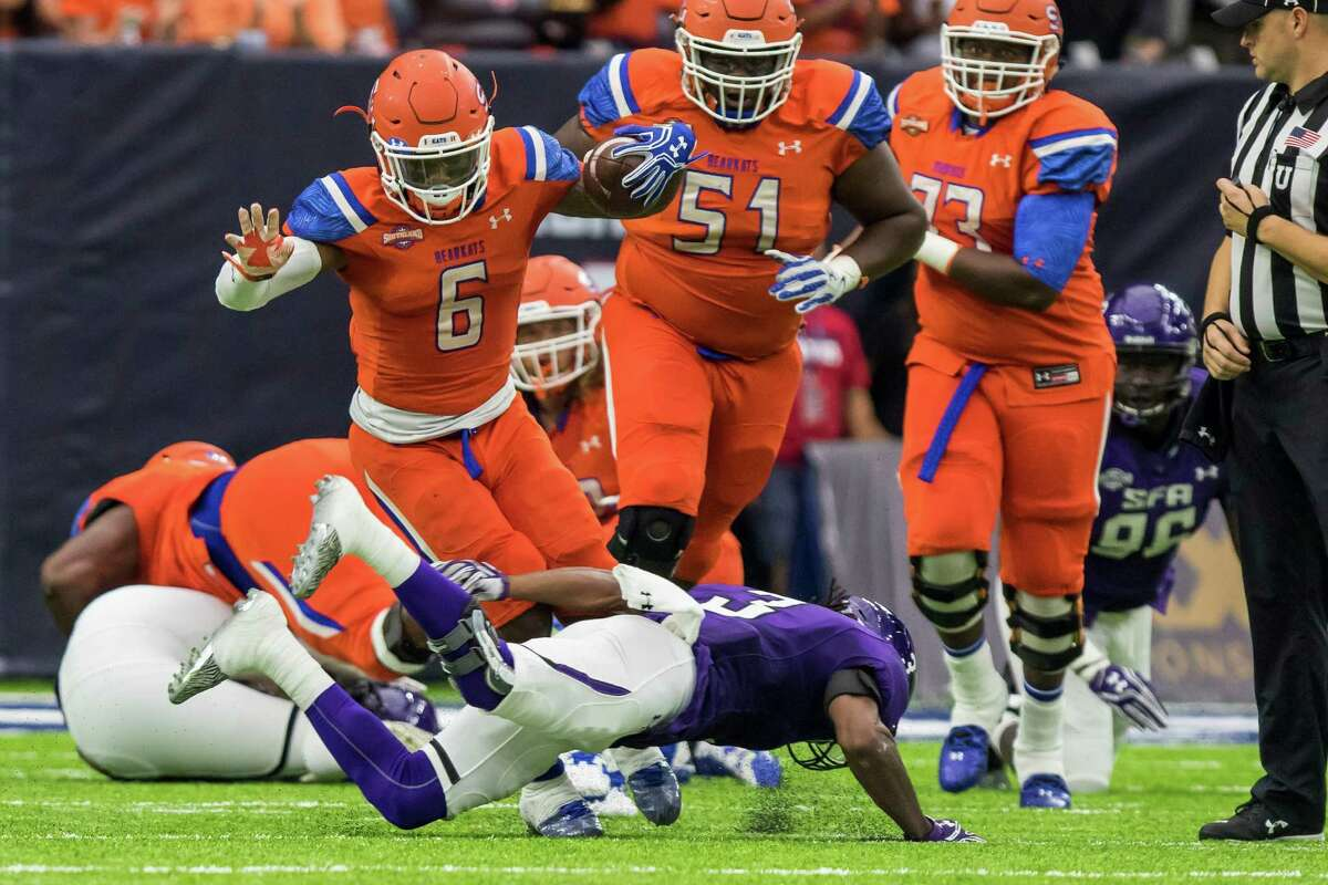 Sam Houston State running back Corey Avery (6) is tripped up after a short gain by Stephen F. Austin defensive back germod Williams (3) in the Battle of the Piney Woods, NCAA Football Championship Subdivision football game at NRG Stadium on Saturday, October 1, 2016, in Houston. (Joe Buvid / For the Houston Chronicle)