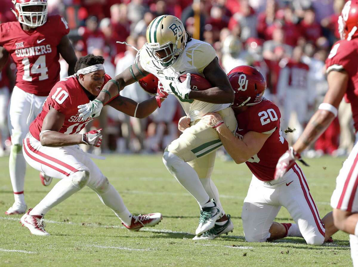 Baylor wide receiver Ishmael Zamora (8) is tackled by Oklahoma safety Steven Parker (10) and linebacker Ruben Hunter (20) during the second half of a NCAA college football game in Norman, Okla. on Saturday, Nov. 12, 2016. Oklahoma won 45-24. (AP Photo/Alonzo Adams)