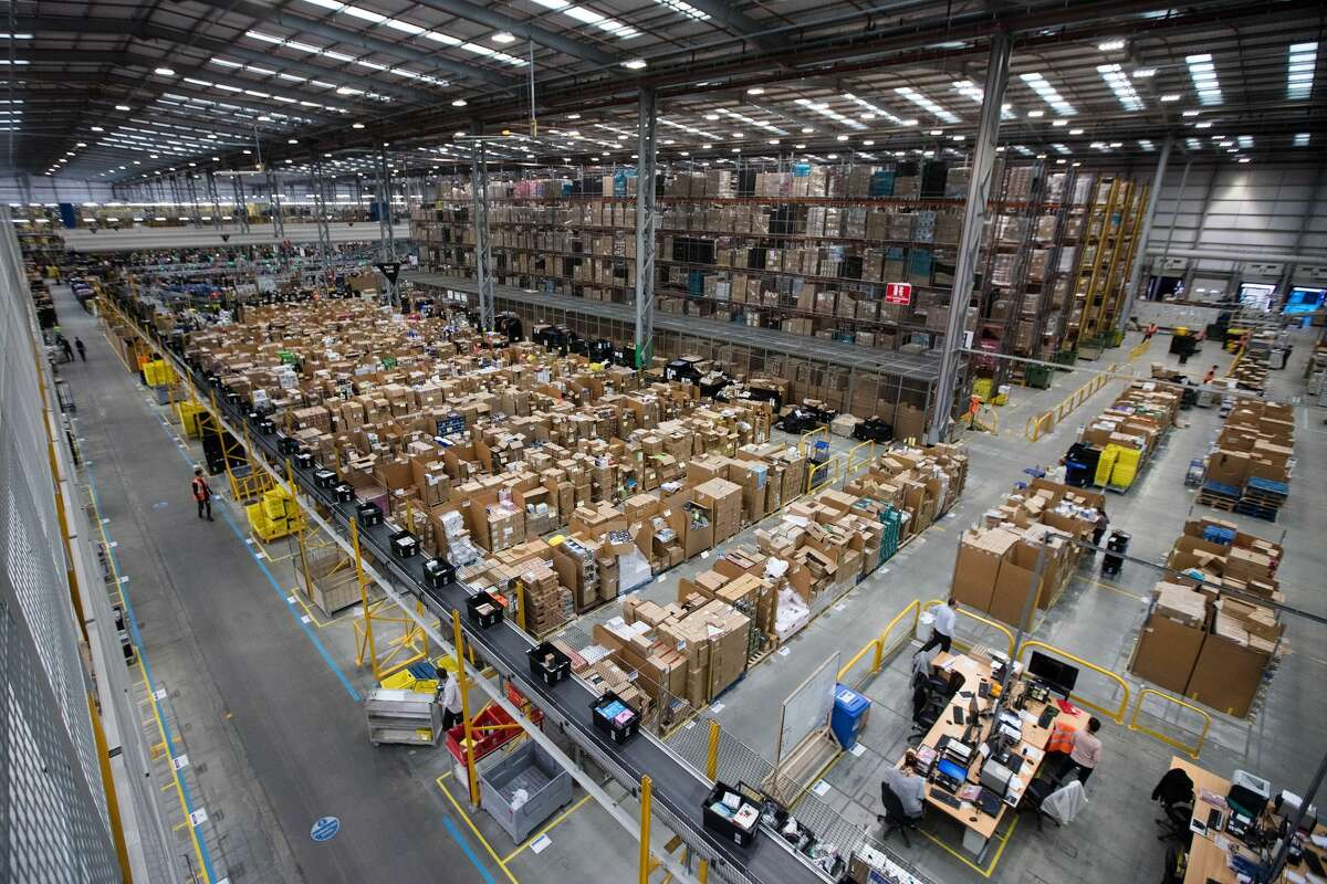 Employees process customer orders ahead of shipping at an Amazon.com Inc. fulfillment center in Peterborough, U.K., on Tuesday, Nov. 15, 2016. The online retail giant needs smart engineers to help expand its cloud computing division, automate warehouses and develop new gadgets like the voice activated Echo speaker. Photographer: Simon Dawson/Bloomberg