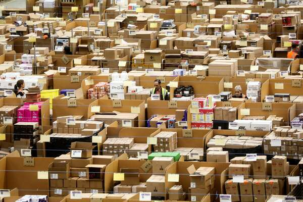 Employees work on the warehouse floor at an Amazon.com Inc. fulfillment center in Peterborough, U.K., on Tuesday, Nov. 15, 2016. The online retail giant needs smart engineers to help expand its cloud computing division, automate warehouses and develop new gadgets like the voice activated Echo speaker. Photographer: Simon Dawson/Bloomberg