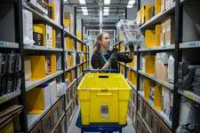 An employee scans merchandise as she collects items for a customer's delivery order from an Amazon.com Inc. fulfillment center in Peterborough, U.K., on Tuesday, Nov. 15, 2016. The online retail giant needs smart engineers to help expand its cloud computing division, automate warehouses and develop new gadgets like the voice activated Echo speaker. Photographer: Simon Dawson/Bloomberg