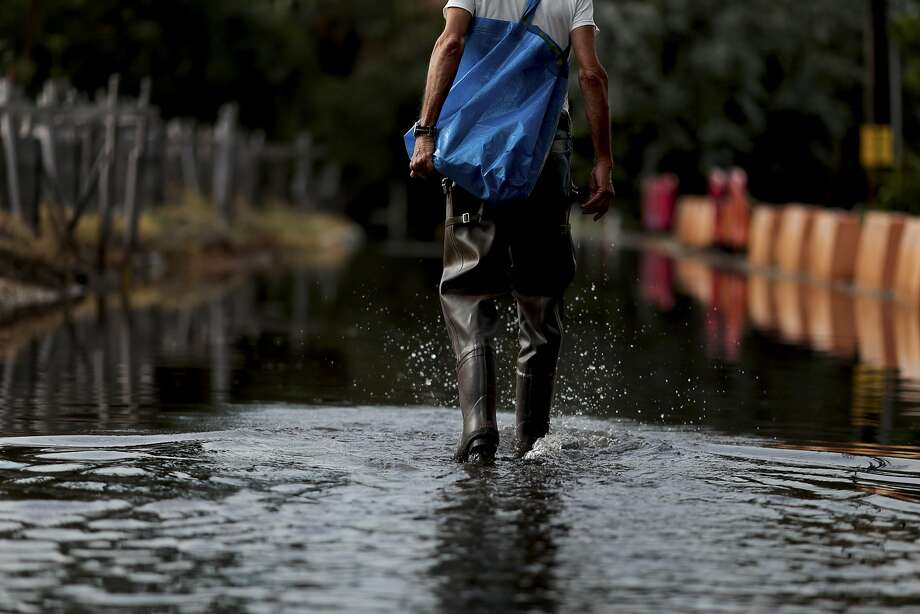 A man walks through floodwaters at a construction site caused by king tides in Fort Lauderdale, Fla. Photo: SCOTT MCINTYRE, NYT