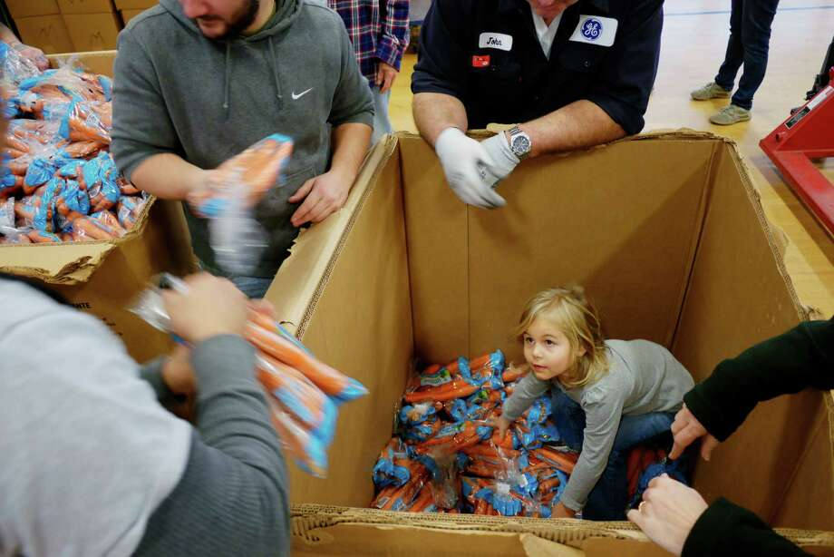 Jessie Pirigyi, 4, of Glenville helps to reach the bags of carrots at the bottom of a box at Keane Elementary School during the Concerned for the Hungry Thanksgiving food drive on Thursday, Nov. 17, 2016, in Schenectady, N.Y.  On Sunday families will receive food boxes with all the items for a traditional Thanksgiving meal along with food for additional meals.  On Thursday volunteers sorted through food.  This is the 38th year of the organizationOs food drive, where they will be feeding over 10,000 people.  The organization estimates that over half of the people they feed are children.  Volunteers spend seven days gathering food, sorting through it, packing up the boxes for families and then handing out the food.  Volunteers are still needed on Friday and Saturday, and the organization is still in need of turkeys, Thanksgiving food items and monetary donations.  Information can be found on their website, www.ConcerForTheHungry.org.  The food drive started 38 years ago with four volunteers who packaged up 300 meals.    (Paul Buckowski / Times Union) Photo: PAUL BUCKOWSKI / 40038123A