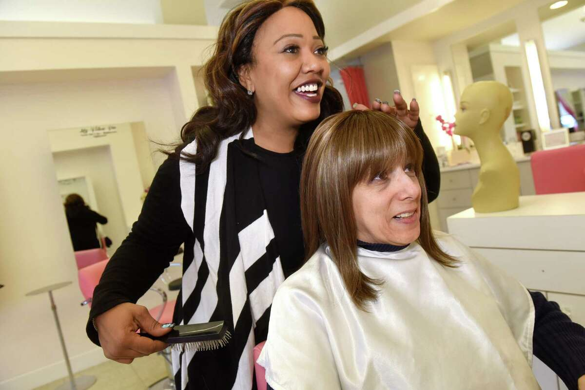 Kathy Marin of Valatie, right, tries on her wig with assistance from Kimberly