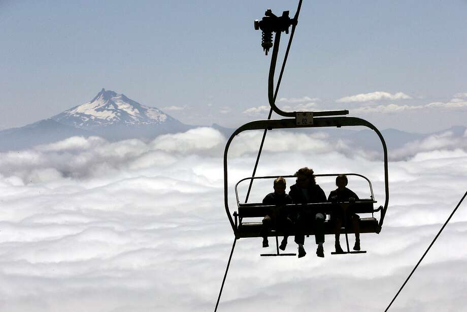 People on the Magic Mile ski lift at Timberline Lodge on Mount Hood are silhouetted against a scenic backdrop of low-lying clouds with Oregon's Mount Jefferson on the horizon near Government Camp, Ore., Wednesday, Aug. 16, 2006. The lift is open all summer to take people well above timberine for hiking, sight-seeing, skiing and snowboarding. (AP Photo/Don Ryan) Photo: DON RYAN, AP