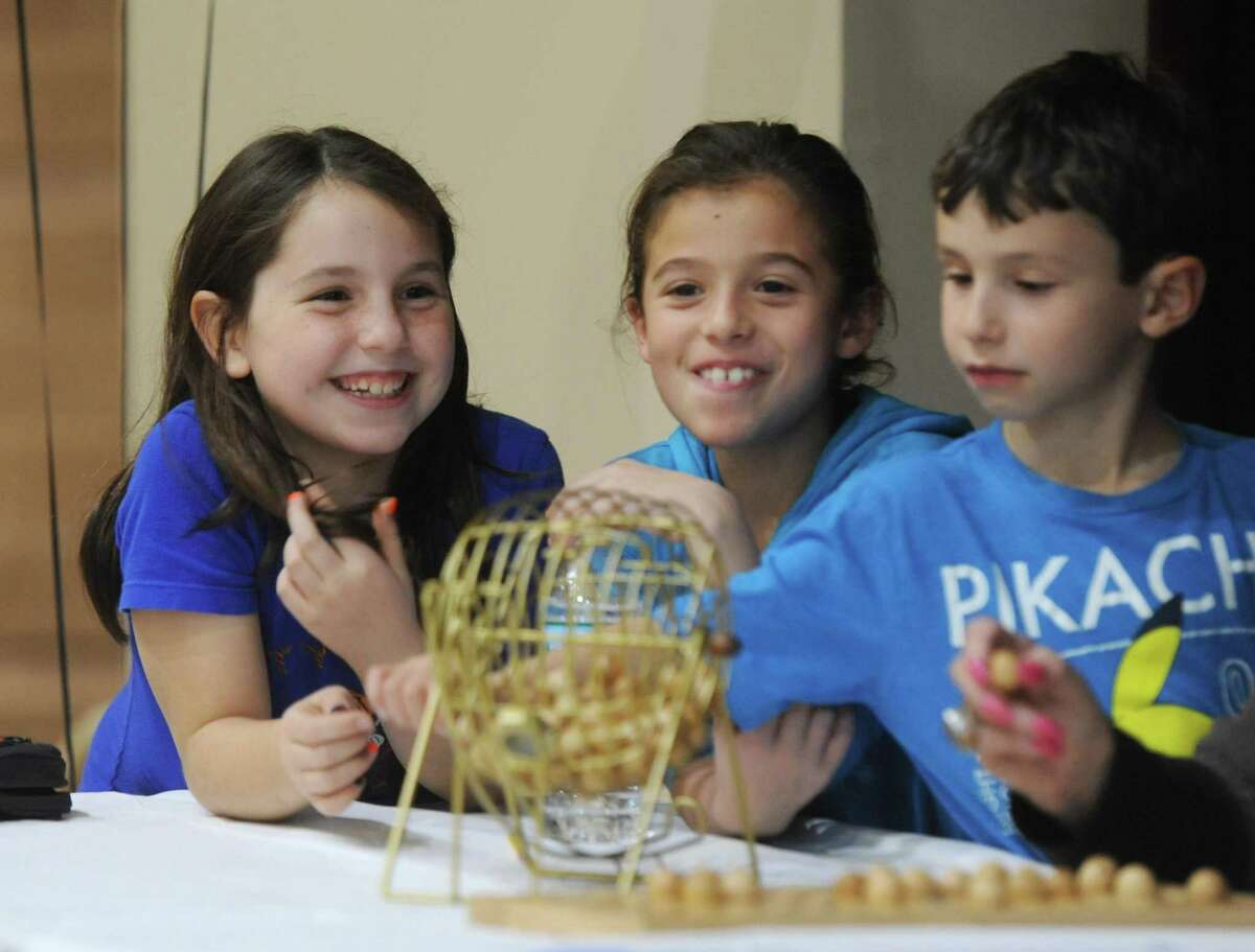 Greenwich kids Hannah Hochman, left, 9, Sarah Goldstein, 8, and Judah Hochman, 7, pick the numbers to be called during Senior Bingo Day at Temple Sholom in Greenwich, Conn. Sunday, Nov. 13, 2016. More than 100 seniors gathered to play Bingo, with each round being a different variation of the game such as straight line and postage stamp. The group was treated to a short performance by the Temple Sholom Youth and Junior Choir.