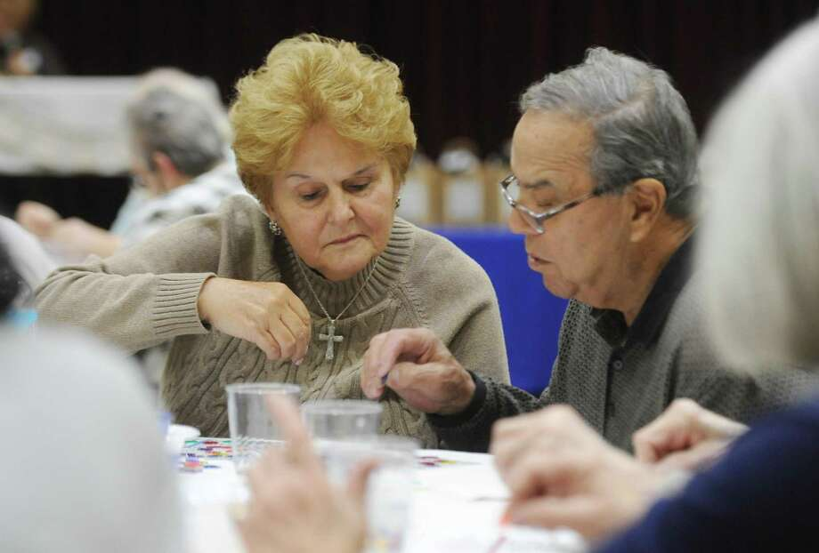 Joan and Charles Shibetti, of Riverside, play Bingo during Senior Bingo Day at Temple Sholom in Greenwich, Conn. Sunday, Nov. 13, 2016. More than 100 seniors gathered to play Bingo, with each round being a different variation of the game such as straight line and postage stamp. The group was treated to a short performance by the Temple Sholom Youth and Junior Choir. Photo: Tyler Sizemore / Hearst Connecticut Media / Greenwich Time
