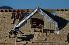 SAN RAFAEL, CA - NOVEMBER 17:  A worker stands on the roof of a home under construction at a new housing development on November 17, 2016 in San Rafael, California. According to a report by the Commerce Department, housing starts surged 25.5% in October to an annual rate of 1.323 million.  (Photo by Justin Sullivan/Getty Images)