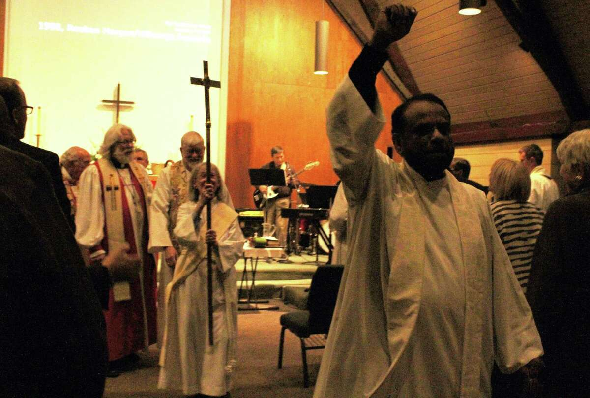 Rev. Canon George Kovoor moves and shakes to the music at the close of the celebration of his new ministry at St. Paul's Church.