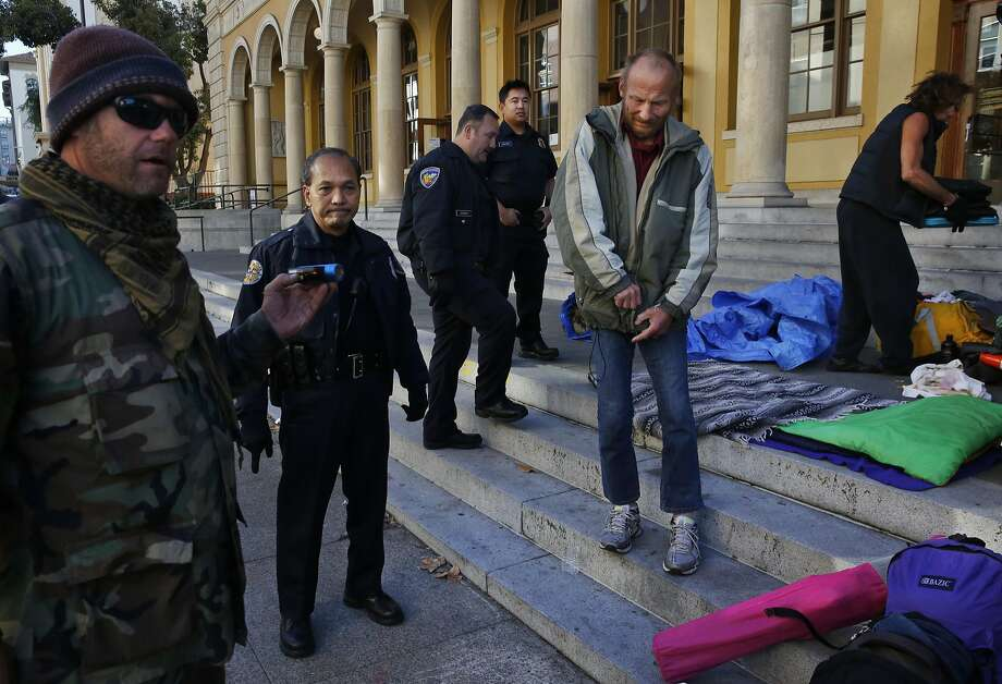 Postal police officers watch as James Cartmill, left, and Jen — member of a homeless camp dubbed First they Came for the Homeless — pack up their remaining belongings with others outside of the Berkeley Post Office on Allston Way after they were removed from their spot across the street earlier in the morning by Berkeley police officers on Nov. 17, 2016. Photo: Leah Millis, The Chronicle