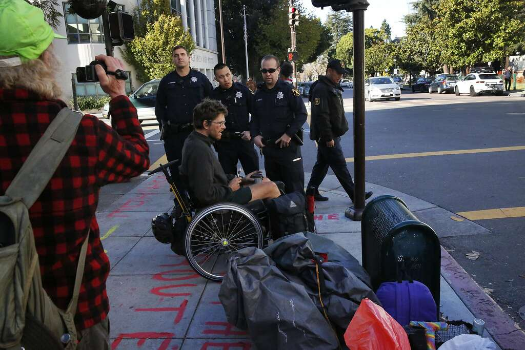 "Berkeley Police officers tell Ben and other members of the homeless camp that they cannot block a sidewalk outside of the US Postal Office on Allston Way after police officers removed a camp earlier in the morning from their spot across the street on Nov. 17, 2016 in downtown Berkeley, Calif. The group of homeless were moved by the Berkeley Police Department from the lawn where they had been camping outside of the Martin Luther King Jr. Civic Center early on Thursday morning. The encampment, which calls itself ""First they Came for the Homeless"" has been protesting the Berkeley food and housing project for weeks. Photo: Leah Millis, The Chronicle"