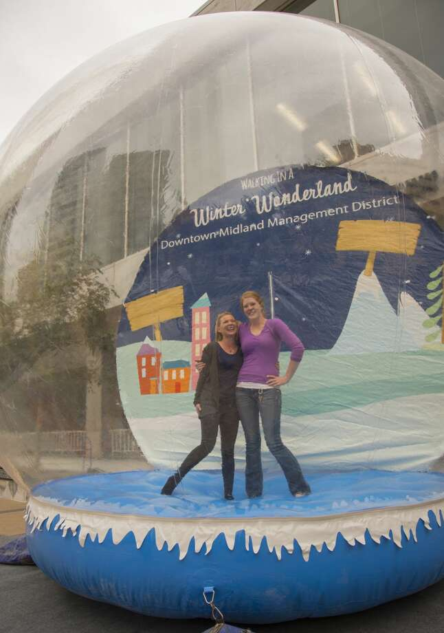 Ashley Huff and Elizabeth McLellan pose in the giant snowglobe Thursday 11-17-16 setup in the Bank of America Plaza. Tim Fischer/Reporter-Telegram Photo: Tim Fischer/Midland Reporter-Telegram
