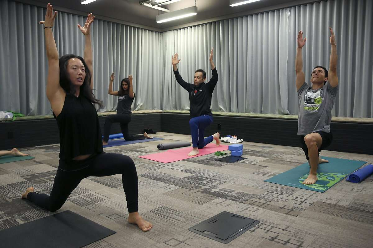 Yoga instructor Kim Sin (left) leads a class for employees in a conference room at Ancestry.com on Townsend Street in San Francisco, Calif. on Thursday, Nov. 17, 2016.