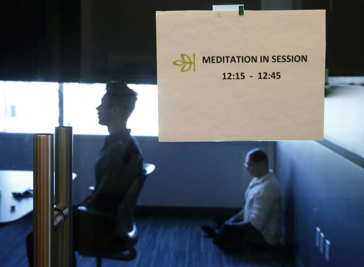 Chad Stose (left) leads a meditation session for employees of Ancestry.com in a conference room at the company's office in San Francisco, Calif. on Thursday, Nov. 17, 2016.