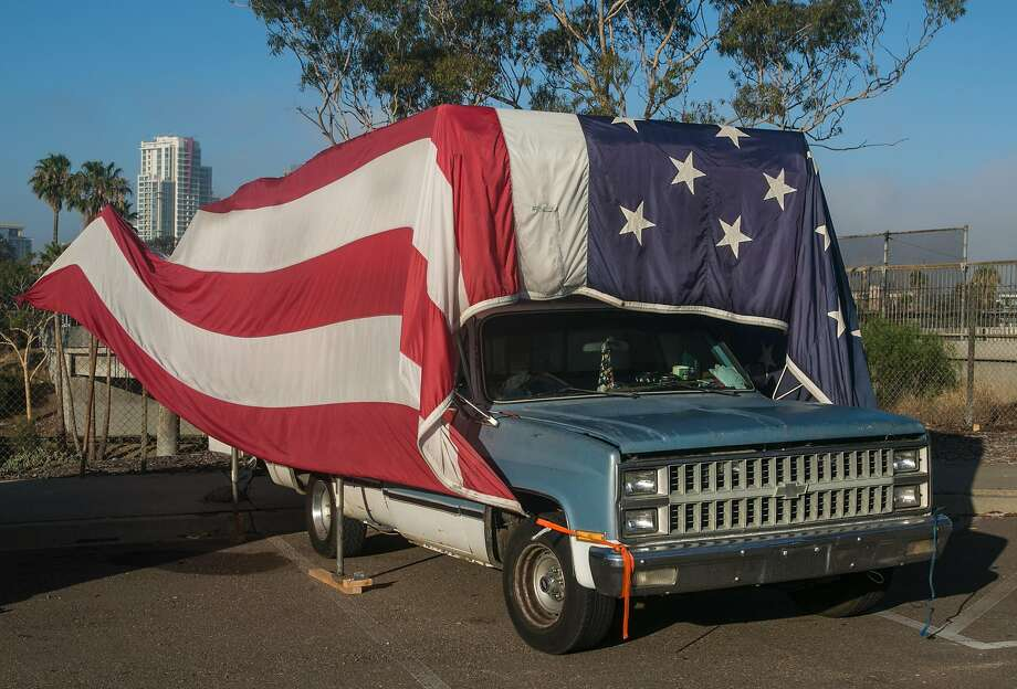 A homeless encampment along Interstate 5 features a truck covered in the American flag on July 23, 2016, in San Diego. Photo: George Rose / Getty Images