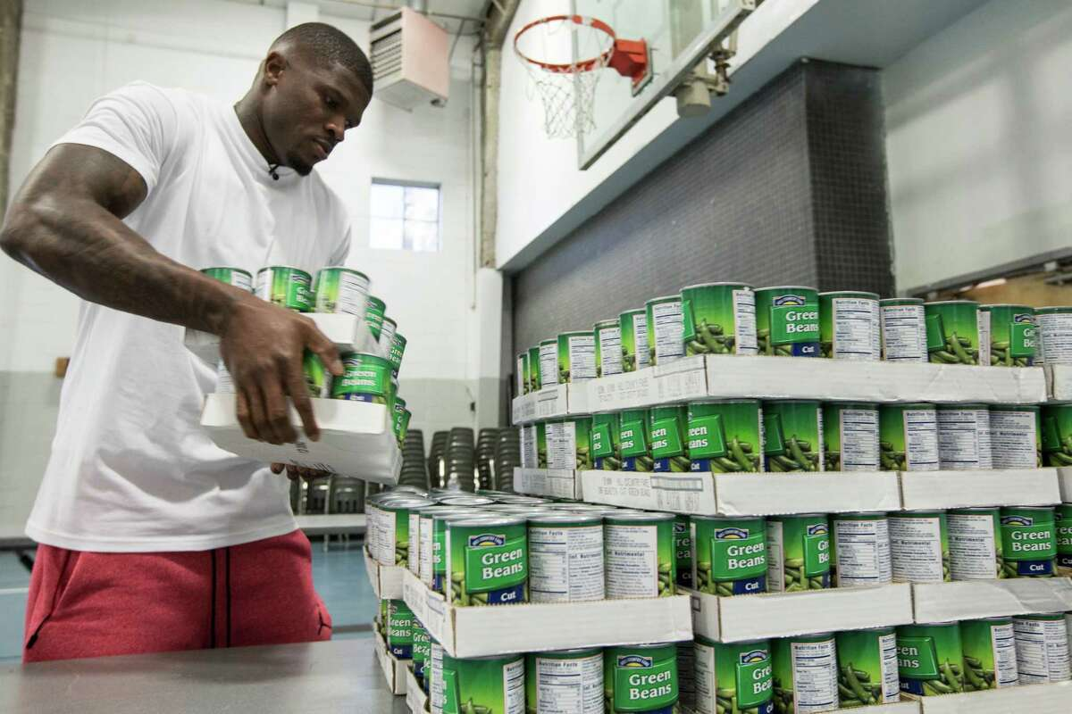 Former Houston Texans wide receiver Andre Johnson helps unload a truck filled with food for the 1500 Thanksgiving meals that will be distributed to indigent families at the Fifth Ward Church of Christ on Thursday, Nov. 17, 2016, in Houston. Johnson was joined by former Texans linebacker Demeco Ryans and church members to unload and sort through the food items to be distributed on Friday.