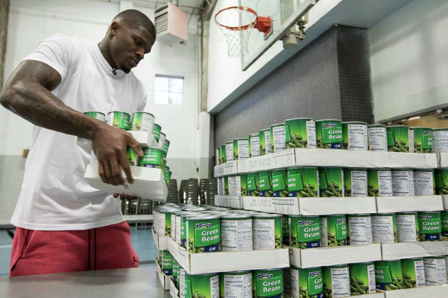 """On Thursday, Nov. 17, former Texans wide receiver Andre Johnson helps unload a truck filled with food for the 1500 Thanksgiving meals to be distributed to indigent families at the Fifth Ward Church of Christ. Johnson was joined by former Texans linebacker Demeco Ryans and church members to unload and sort the food items.  """"This is our way of helping feed those in need and spreading our spirit of gratitude and kindness, because it's a privilege for us to be able to give,"""" Johnson said. Photo: Brett Coomer, Houston Chronicle / © 2016 Houston Chronicle"""