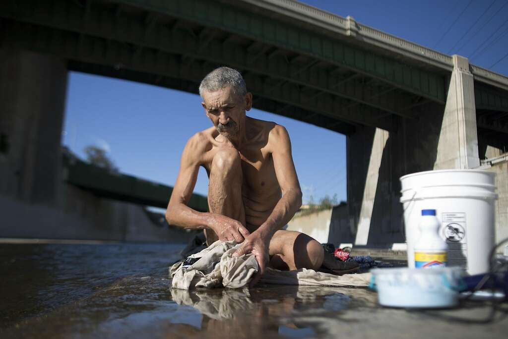 LOS ANGELES, CA - NOVEMBER 20: Fernando Lopez bathes and does laundry in the Los Angeles River on November 20, 2015 in Los Angeles, California. With the approach of devastating winter storm conditions due to the growing predicted El Nino weather effect, and an affordable housing crises and rapidly growing homeless population in Los Angeles, the L.A. City Council has declared a shelter crisis to help homeless residents. Many of the estimated 26,000 homeless in L.A. live in riverbeds and storm drains that could quickly turn deadly during powerful storms. The council stopped short of declaring a state of emergency as members had promised in September. (Photo by David McNew/Getty Images) Photo: David McNew, Getty Images
