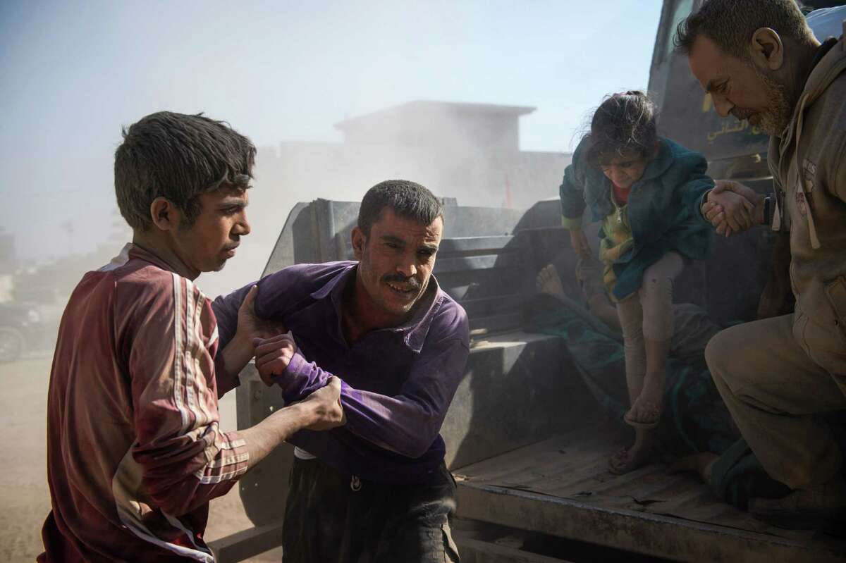 A man with light shrapnel wounds to his leg is helped off an Iraqi Special Forces Humvee at a field clinic Thursday in eastern Mosul.