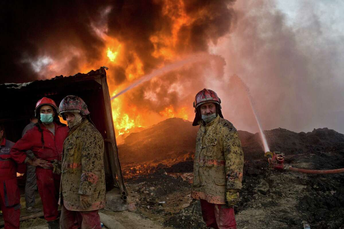 FILE - In this Wednesday, Nov. 9, 2016 file photo, firefighters work at the site of an oil well fire in Qayara, some 31 miles (50 km) south of Mosul, Iraq. As the operation to retake Mosul enters its second month Iraqi forces are preparing for prolonged, grueling urban combat as they slow the tempo of their operation, advancing just a few hundred meters at a time. The individual tactics employed by IS mirror past fights with the group, but the sheer scale of IS defenses and counterattacks in Mosul has overwhelmed IraqÂ?'s military.(AP Photo/Marko Drobnjakovic, File)