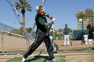 Oakland A's owner Lou Wolf takes a few swings in the batting cage, during morning workouts at Phoenix Municipal Stadium on Tuesday Mar. 12, 2013, in Phoenix, Az., as the Oakland Athletics prepare to take on the Kansas City Royals in Spring Training action.