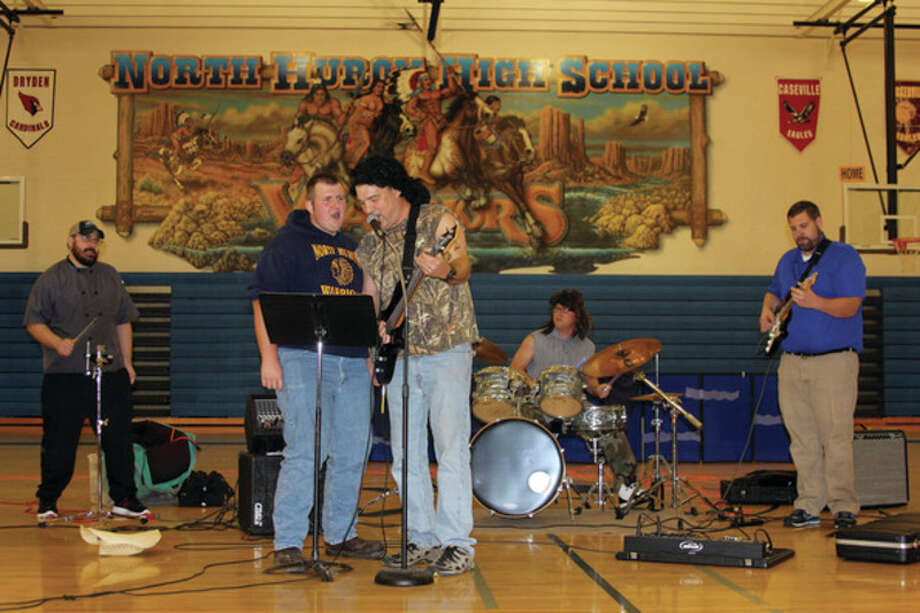 From left, Mark Polega, junior Tom Toner, Darin McNabb, Chad Knoblock and Steve McIntosh -- better known as Ted Nugent and the Button Bucks -- jam out to Nugent's hit classic 'Fred Bear' during North Huron's talent show Thursday afternoon.