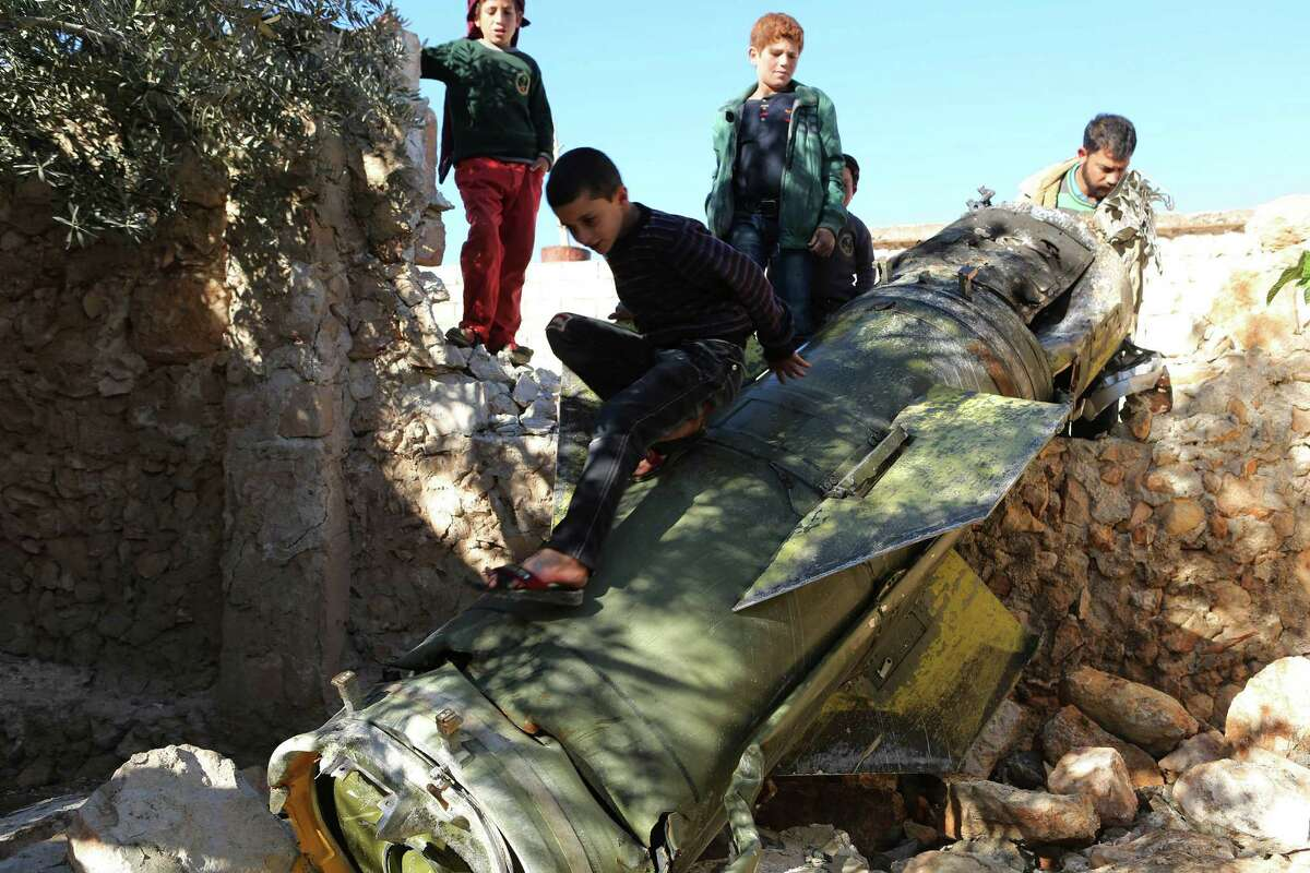 Children play on an unexploded Russian rocket, possibly from a Russian warship, on Thursday in Anjara, a village west of Aleppo, Syria. Russia and Turkey ar expected to expand their military operations in Syria, experts say.