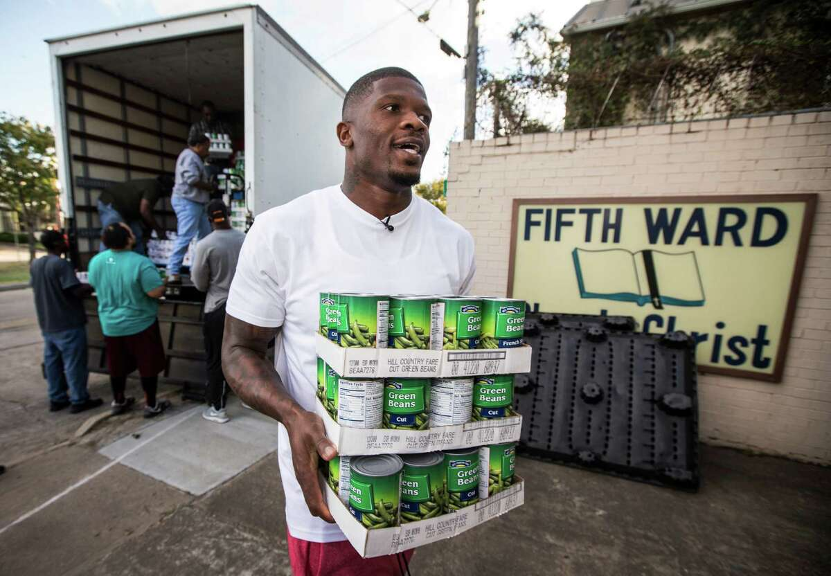 Ex-Texans receiver Andre Johnson helps unload food at the Fifth Ward Church of Christ on Thursday that will be distributed to needy families Friday.