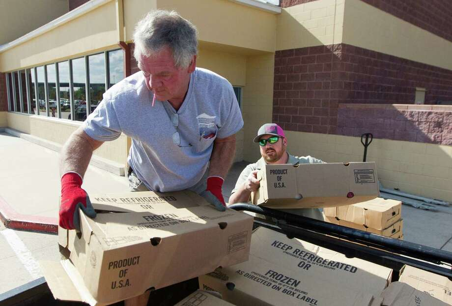 Gerald Nowak helps load 80 frozen turkeys, donated by a couple that wished to remain anonymous, onto a truck at Walmart on Texas 242 and Interstate 45 Thursday in Conroe. The event will run from 10:30 a.m. to 2 p.m. Thanksgiving Day, Thursday, Nov. 24, at the Exhibition Building at the Montgomery County Fairgrounds. Photo: Jason Fochtman, Staff Photographer / Houston Chronicle