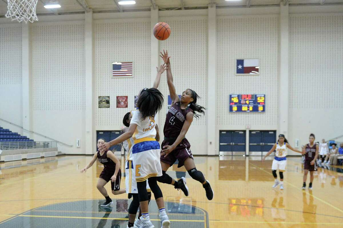 Lacee Savage (4) of Clear Creek attempts a shot over multiple Elkins defenders during the overtime period of a basketball game between the Clear Creek Wildcats and the Elkins Knights during the Ft. Bend ISD Varsity Girls Tournament on Thursday November 17, 2016 at the Buddy Hopson Field House, Missouri City, TX.