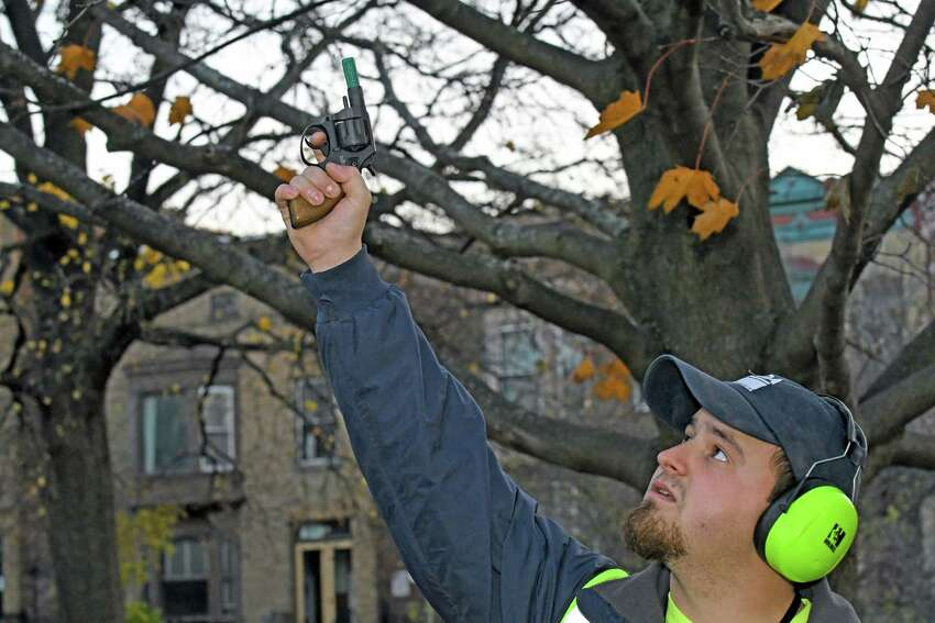 U.S. Department of Agriculture wildlife specialist Tyler DeLisle demonstrates the use of a blank pistol thats shoots with the sound of a bird whistle and pyrotechnics to scare crows at Washington Park on Thursday Nov. 17, 2016 in Albany N.Y. (Michael P. Farrell/Times Union)