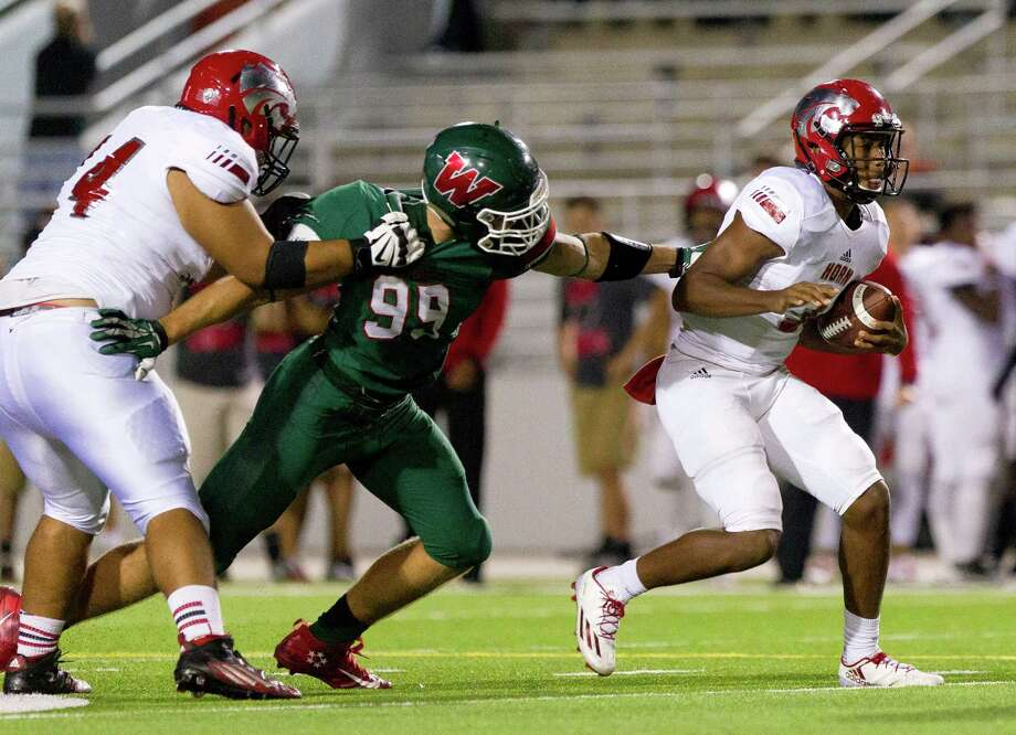 The Woodlands defensive linemen Michael Purcell (99) reaches to slow down Mesquite Horn quarterback Jermaine Givens (3) during the third quarter of a Region II-6A Division I bi-district playoff game at Woodforest Bank Stadium Friday, Nov. 11, 2016, in Shenandoah. Photo: Jason Fochtman, Staff Photographer / Houston Chronicle