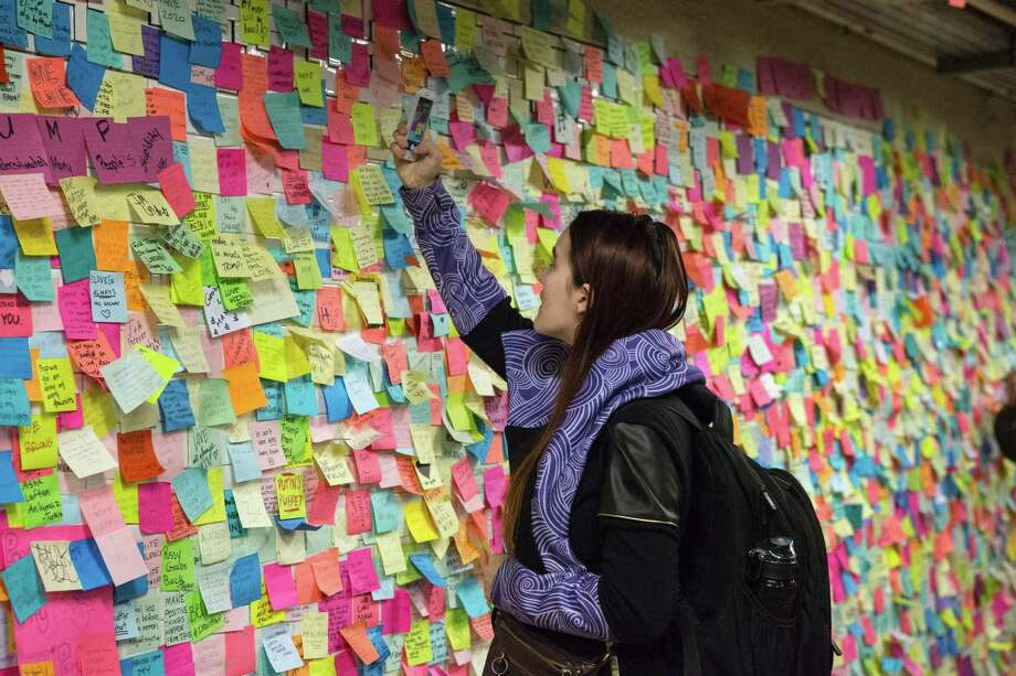 """A woman sticks a Post-It note to participate in the art piece 'Subway Therapy' at the Union Square subway station in New York on November 17, 2016 """"Subway Therapy"""" allows people to express their thoughts with the public, and began after the November 8, 2016 US presidential election. / AFP PHOTO / KENA BETANCURKENA BETANCUR/AFP/Getty Images Photo: KENA BETANCUR / AFP or licensors"""