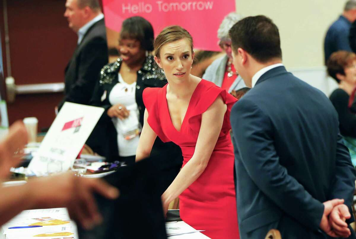 Job recruiters work their booths at a job fair in Pittsburgh earlier this year. On Thursday, the Labor Department reported that the number of applications for unemployment benefits in the previous week fell to its lowest level in more than four decades.