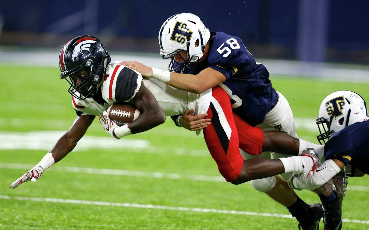 Westfield wide receiver Jaylon Garrett (4) dives forward as he is hit by Round Rock Stony Point linebacker Jack Landry (58) and defensive back Jaylen Walther (9) after a recetion during the third quarter of a Class 6A, Division II, high school football playoff game at NRG Stadium on Thursday, Nov. 17, 2016, in Houston.