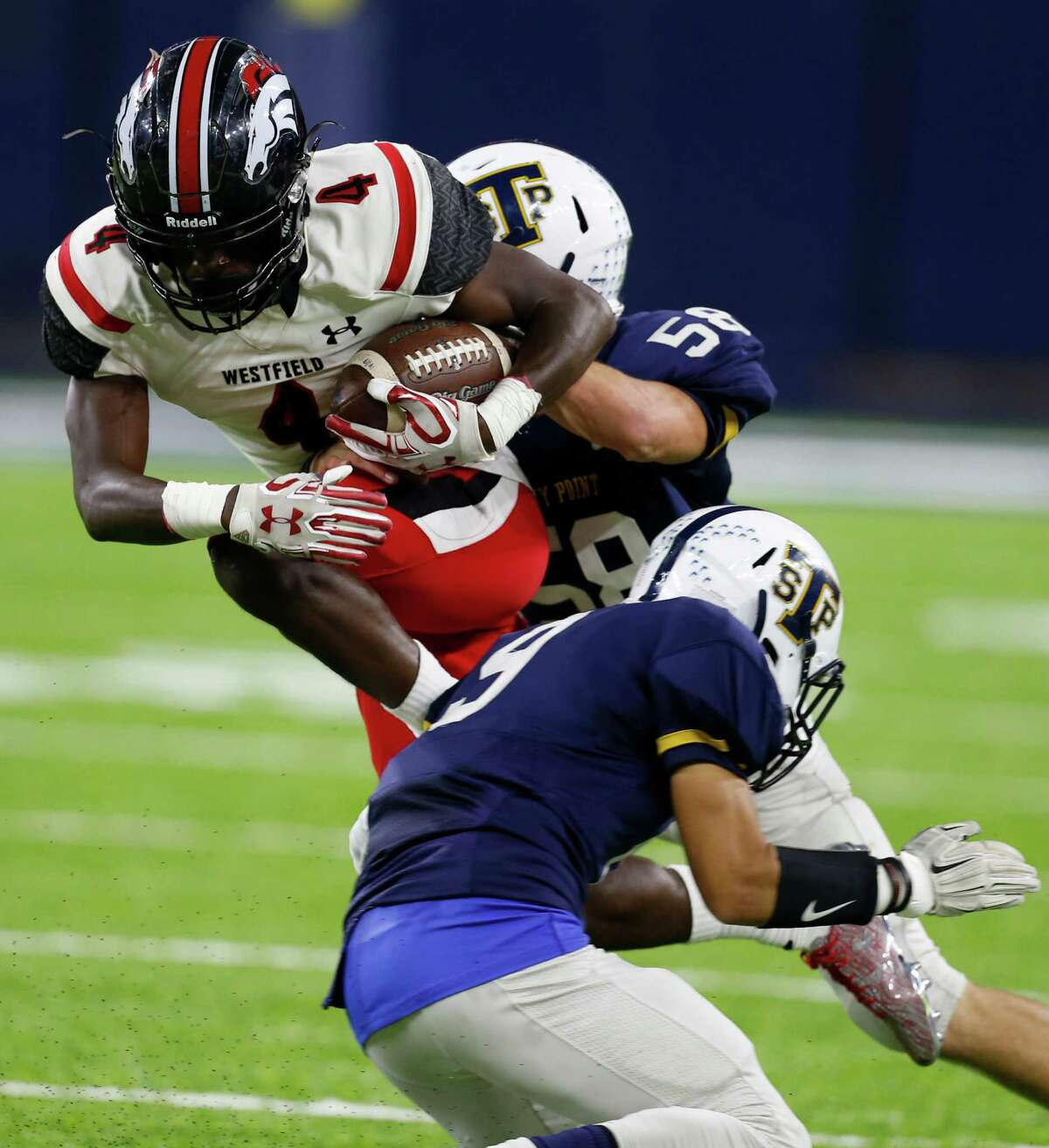 Westfield wide receiver Jaylon Garrett (4) runs between Round Rock Stony Point linebacker Jack Landry (58) and Round Rock Stony Point defensive back Jaylen Walther (9) after a recetion during the third quarter of a Class 6A, Division II, high school football playoff game at NRG Stadium on Thursday, Nov. 17, 2016, in Houston.