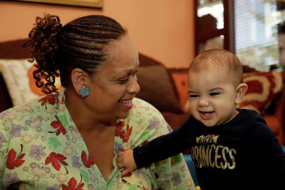 In this Thursday, Oct. 20, 2016, photo, Nancy Harvey, owner of Lil' Nancy's Primary Schoolhouse, left, cares for a toddler at her home, which has she has converted into a child care center, in Oakland, Calif. Most U.S. households are heading for a worse lifestyle in retirement than they had while they were working, because they simply aren't saving enough, experts say. Harvey, who has less than $2,000 saved despite her decades of work, plans to continue with real-estate classes in hopes that it can provide a second job. (AP Photo/Marcio Jose Sanchez) ORG XMIT: CAMS301 Photo: Marcio Jose Sanchez / Copyright 2016 The Associated Press. All rights reserved.