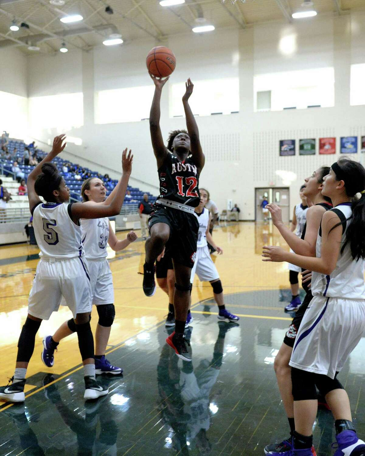 Syndi Rowland (12) of Austin drives to the hoop during the first half of a basketball game between the Ft. Bend Austin Bulldogs and the Jersey Village Falcons during the Ft. Bend ISD Varsity Girls Tournament on Thursday November 17, 2016 at the Buddy Hopson Field House, Missouri City, TX.