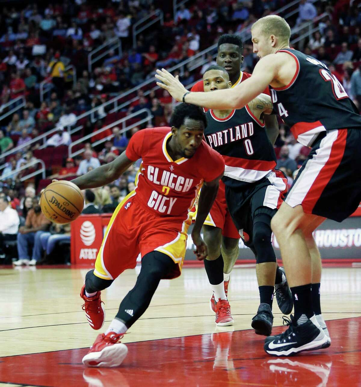 Houston Rockets guard Patrick Beverley (2) drives around Portland Trail Blazers guard Damian Lillard (0) and forward Mason Plumlee (24) in the second half of an NBA basketball game on Thursday, Nov. 17, 2016, in Houston. (AP Photo/Bob Levey)