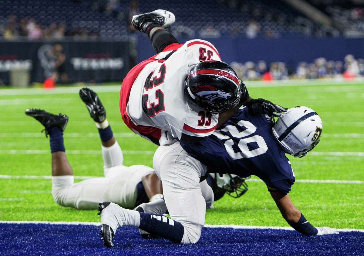 Westfield fullback Jimmy Bruner (33) dives over Round Rock Stony Point defensive back Kytanl Miller (29) on a 1-yard touchdown run in the first half of Thursday's Class 6A Division II playoff game at NRG Stadium.
