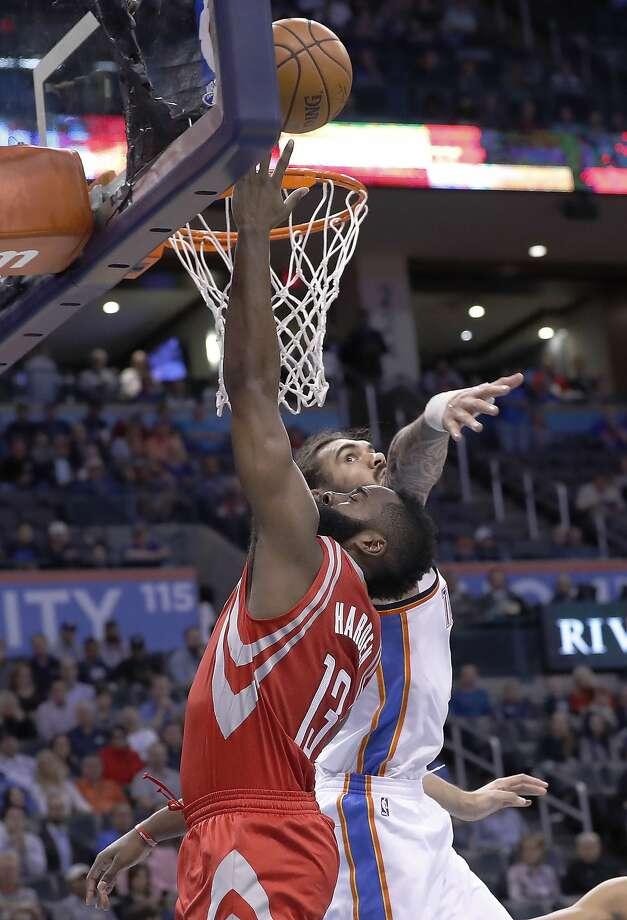 Houston s guard James Harden puts up a shot over Oklahoma City center Steven Adams. Photo: Alonzo Adams, Associated Press