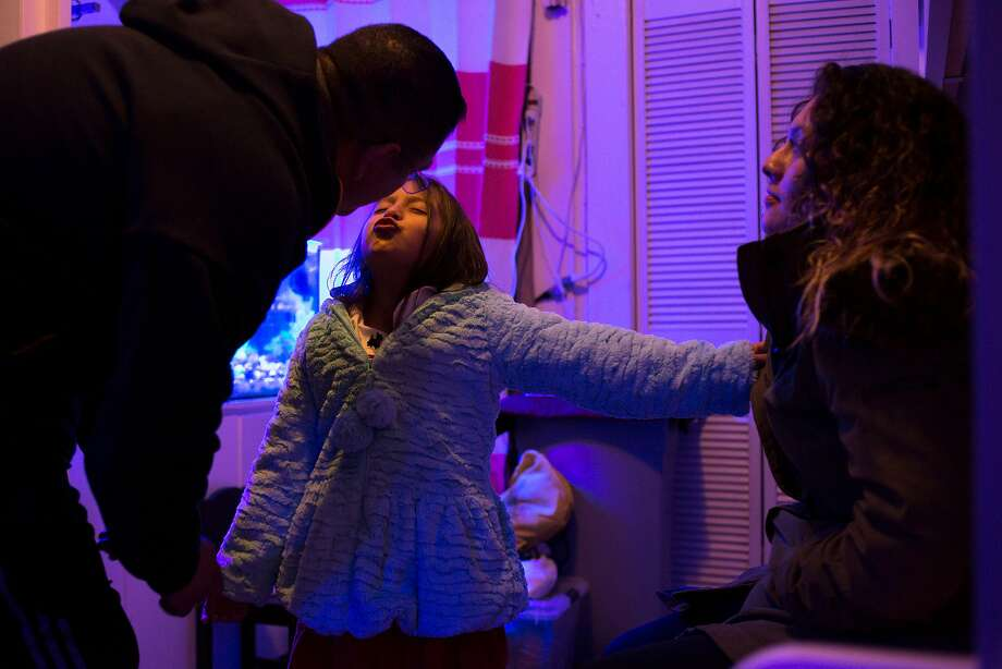 From left: Miguel kisses his six-year-old daughter Luana, at their home, Thursday, Nov. 17, 2016 in San Francisco, Calif. Miguel's oldest daughter, 22-year-old Dayana is seen at right watching the television. Photo: Santiago Mejia, The Chronicle