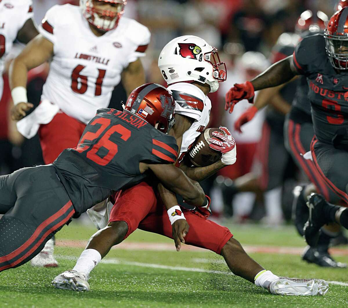 A hit by UH cornerback Brandon Wilson, left, results in Louisville quarterback Lamar Jackson doing the splits. Jackson, who entered Thursday's game a Heisman front-runner, was under constant pressure by the Cougars at TDECU Stadium.