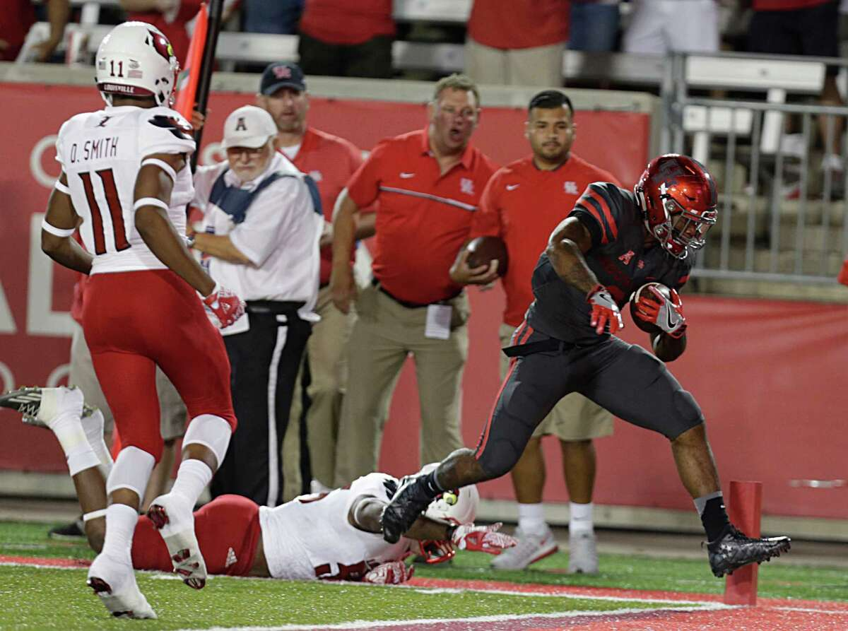 UH running back Duke Catalon, right, outruns diving Louisville linebacker Keith Kelsey to the goal line for a first-half touchdown Thursday night before a record crowd of 42,822 at TDECU Stadium.