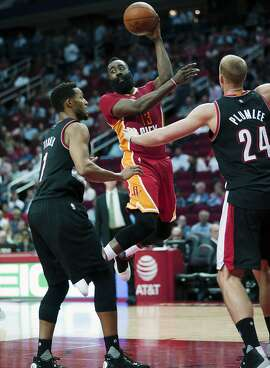Houston Rockets guard James Harden (13) passes the ball as Portland Trail Blazers guard Evan Turner (1) and forward Mason Plumlee (24) defend in the second half of an NBA basketball game on Thursday, Nov. 17, 2016, in Houston. (AP Photo/Bob Levey)
